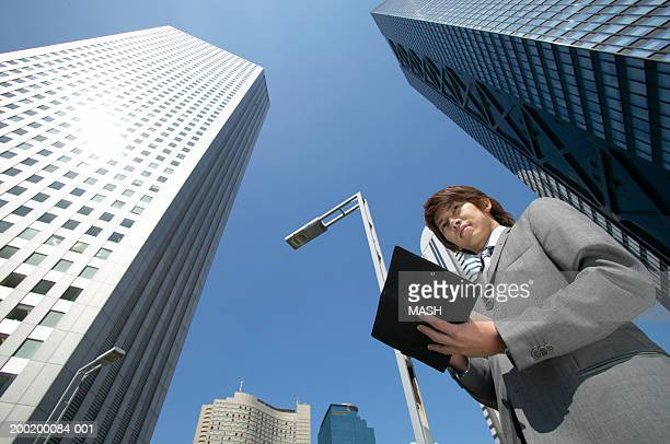 Businessman by skyscrapers, holding personal organiser, low angle view