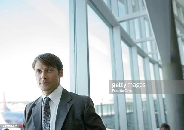 businessman by window in airport - erker stockfoto's en -beelden