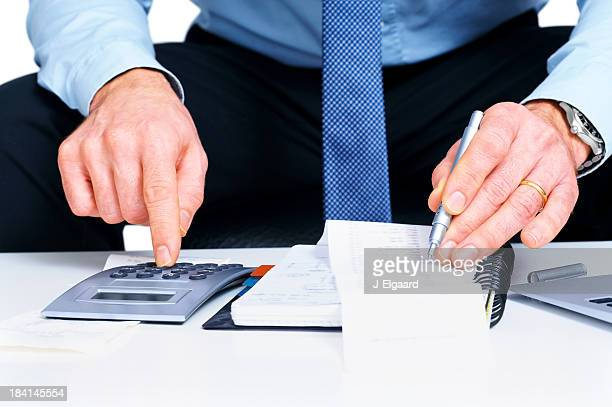 Businessman calculating ther sales figure with calculator