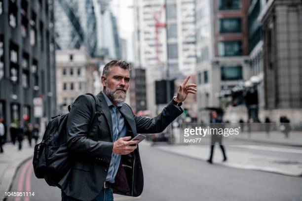businessman calling a taxi in london - taxi foto e immagini stock