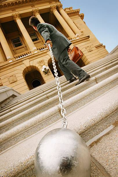 Businessman carrying a ball and chain
