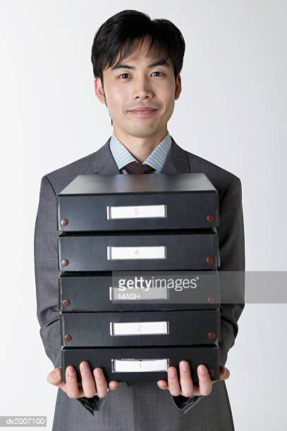 Businessman Carrying a Stack of Filing Boxes