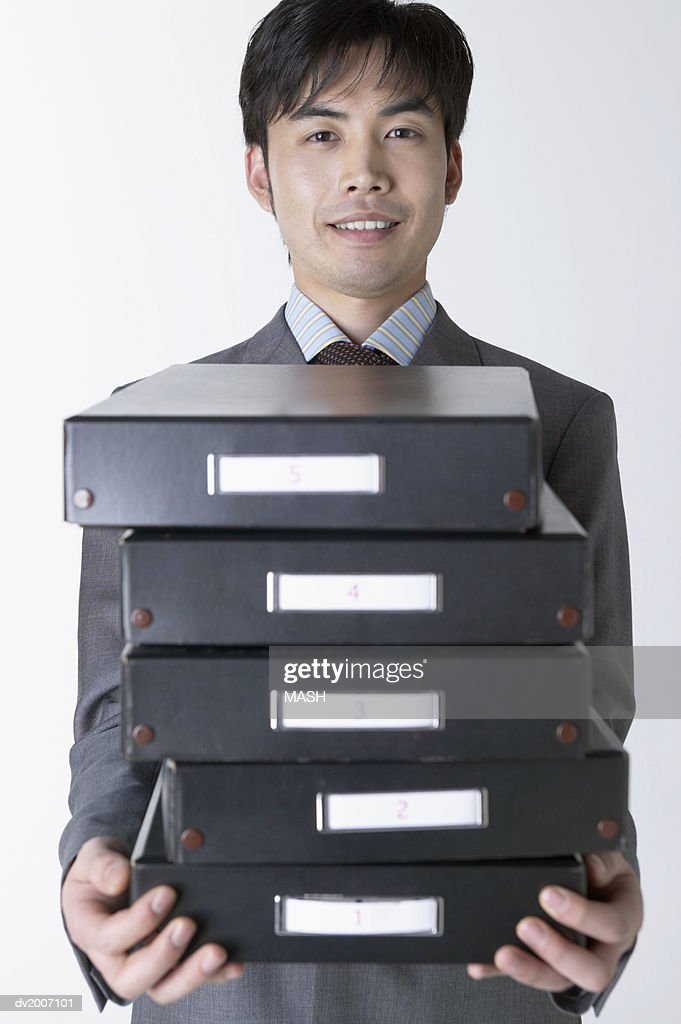 Businessman Carrying a Stack of Filing Boxes : Stock Photo