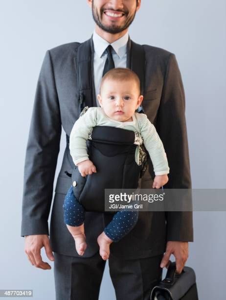 Businessman carrying baby in carrier