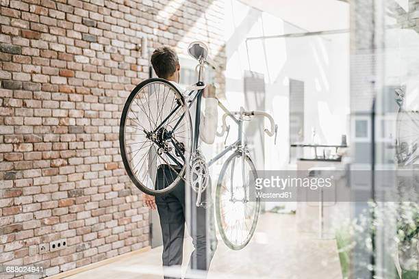 Businessman carrying bicycle in office