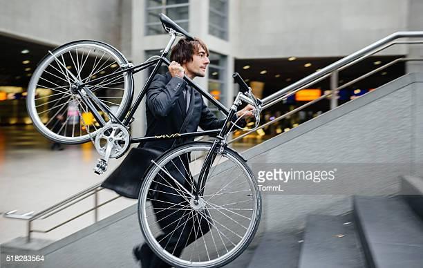 Geschäftsmann, die mit dem Fahrrad auf seiner Schulter