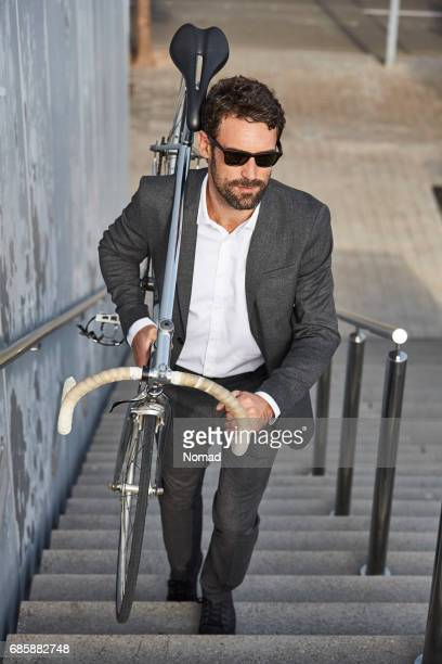 Businessman carrying bicycle on steps in city
