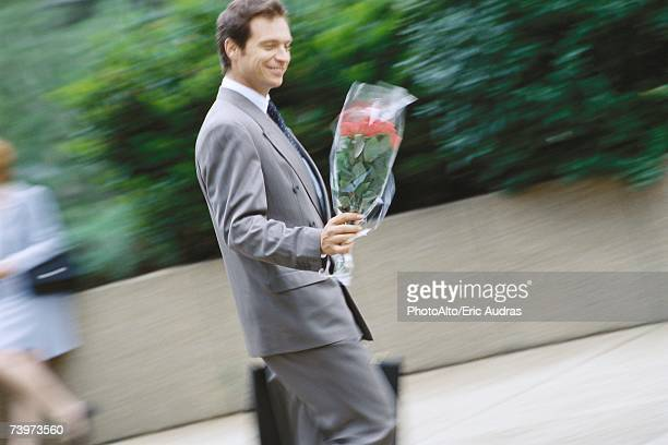 Businessman carrying bouquet of flowers
