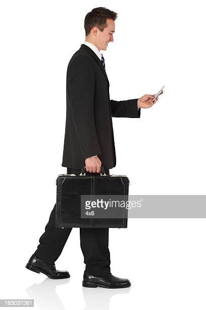 Businessman carrying briefcase and using a mobile phone