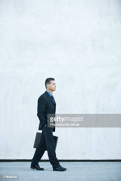 Businessman carrying briefcase, hand in pocket, full length