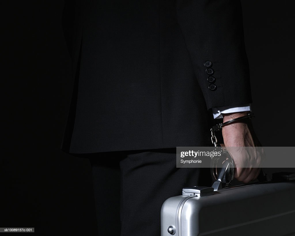 Businessman carrying briefcase locked to handcuff, close up, mid section : Stockfoto