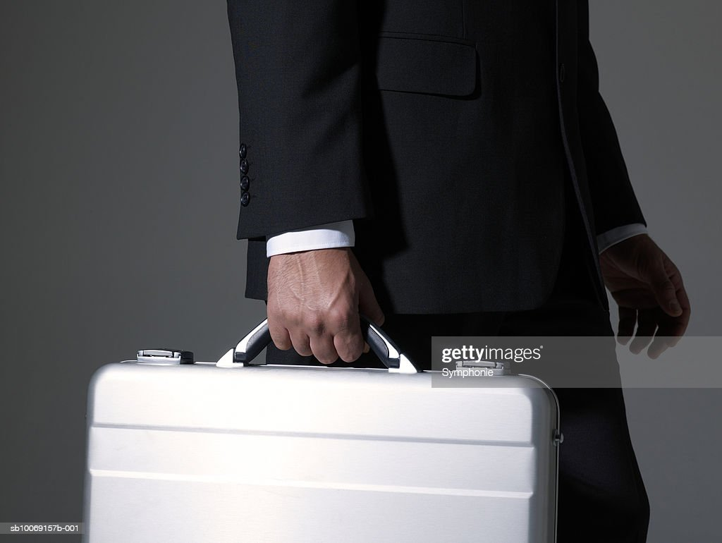 Businessman carrying briefcase, mid section, side view : Stockfoto