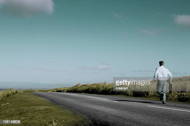 Businessman Carrying Briefcase Running Down Country Road