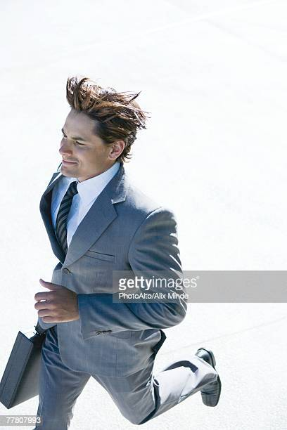 Businessman carrying briefcase, running