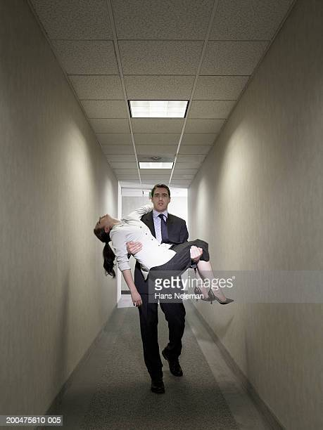 Businessman carrying collapsed businesswoman in corridor