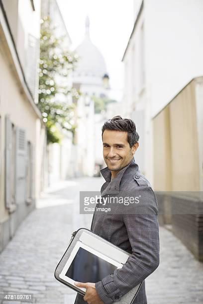 Businessman carrying digital tablet on city street