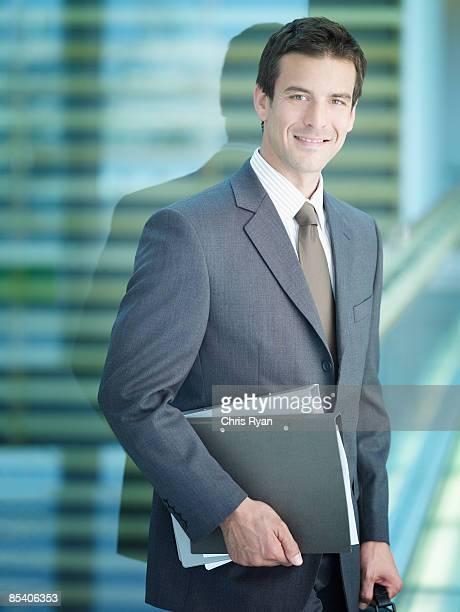 Businessman carrying file folders