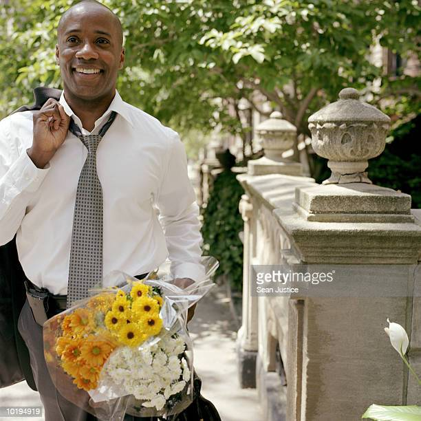 businessman carrying flowers on street - オープンネック ストックフォトと画像