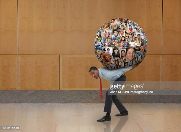 Businessman carrying globe on his back