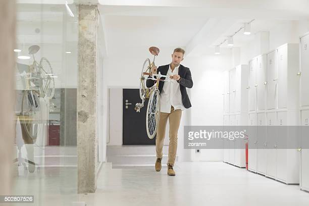 Businessman carrying his bicycle in office