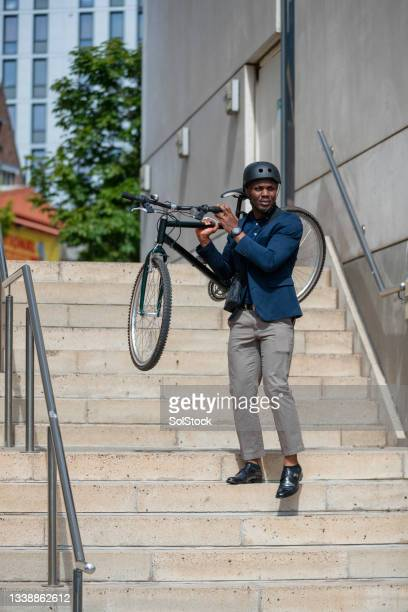 businessman carrying his bicycle - green blazer stock pictures, royalty-free photos & images