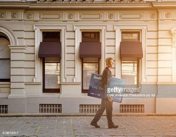 Businessman carrying large credit card on city street