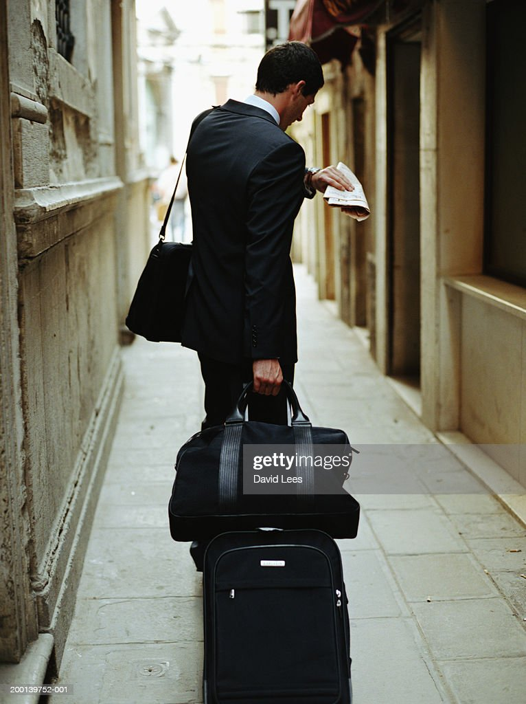 Businessman carrying luggage, looking at watch, rear view : Stock Photo