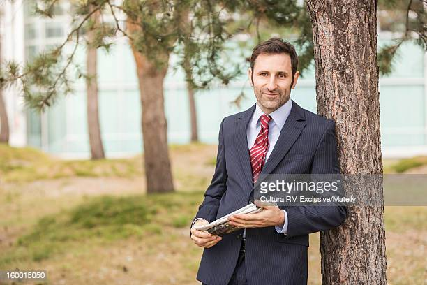 Businessman carrying newspaper in park