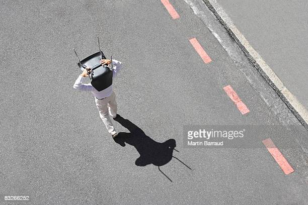 Businessman carrying office chair in roadway