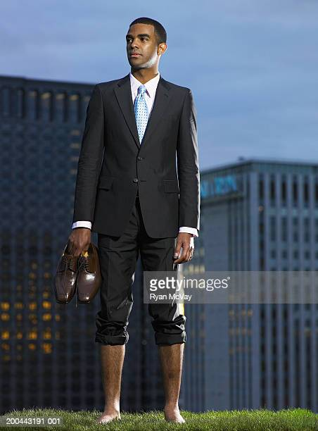 businessman carrying shoes in grass field - hairy legs stock photos and pictures
