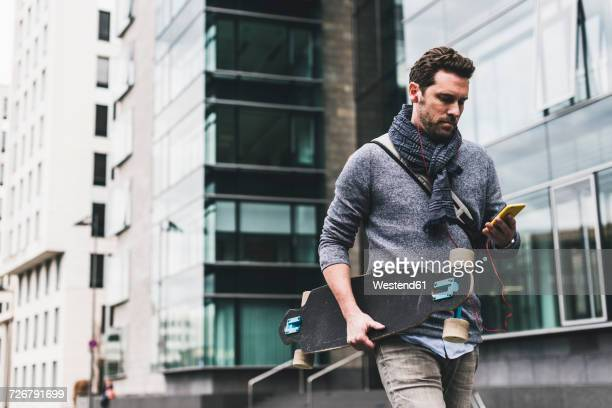 businessman carrying skateboard, using smartphone and earphones - one mature man only stock pictures, royalty-free photos & images