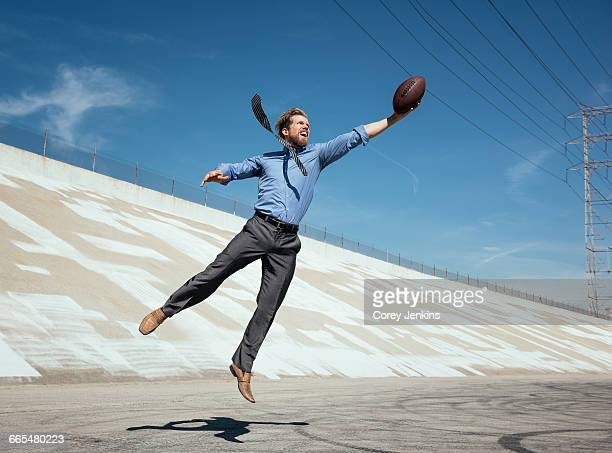 businessman catching american football on los angeles river, california, usa - businesswear stock pictures, royalty-free photos & images