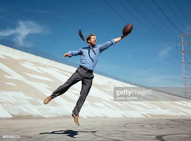 businessman catching american football on los angeles river, california, usa - fangen stock-fotos und bilder
