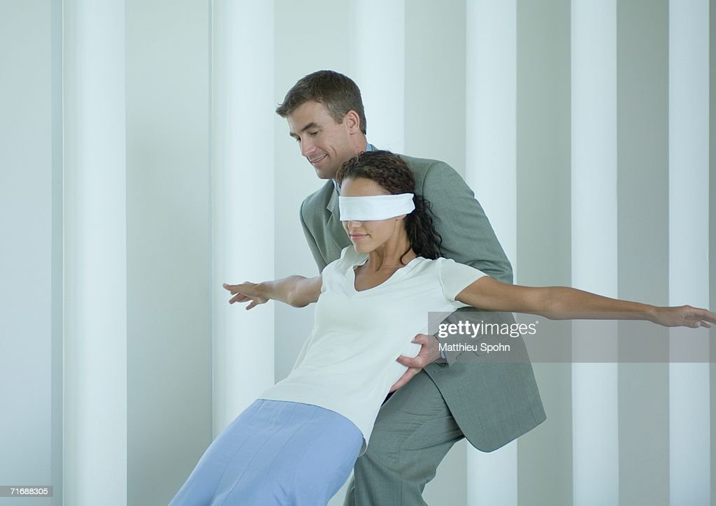 Businessman catching blindfolded woman : Stock Photo