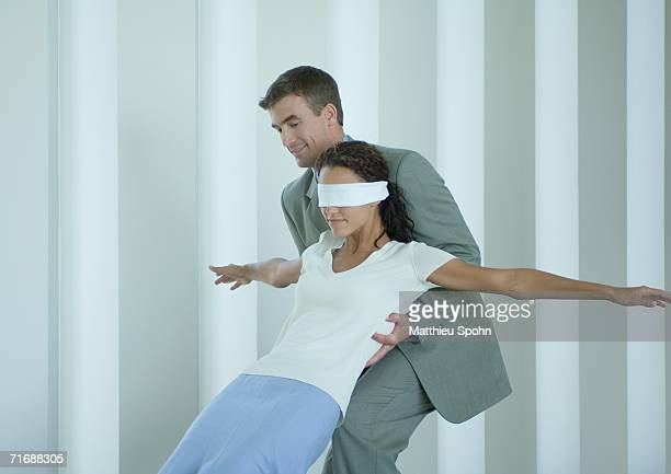 Businessman catching blindfolded woman
