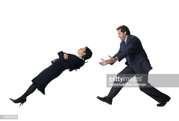businessman catching falling businesswoman - bending over backwards stock photos and pictures