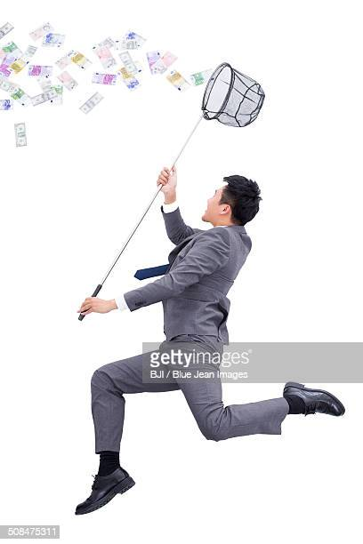 Businessman catching money with butterfly net