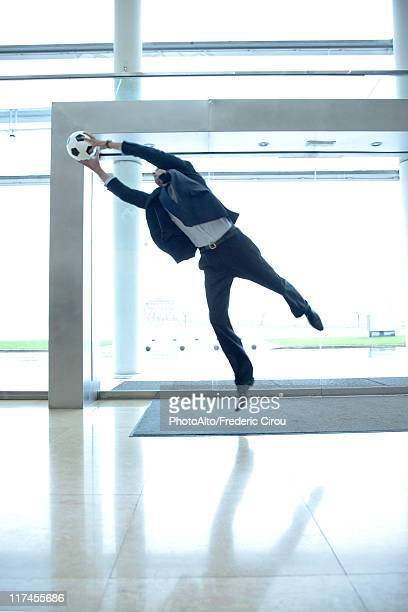 Businessman catching soccer ball in lobby