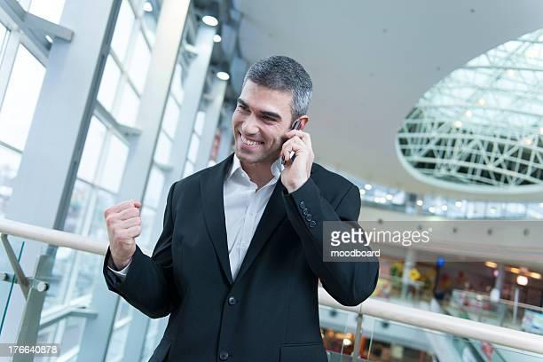Businessman celebrates talking on mobile phone
