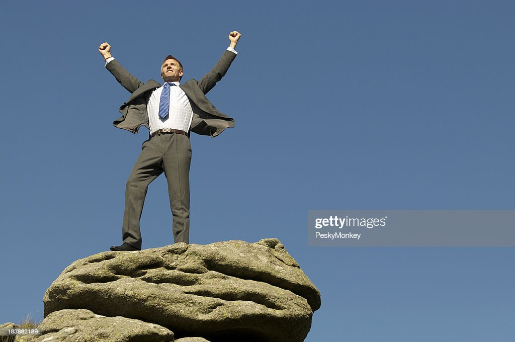 Businessman Celebrates Victory on Rocky Mountaintop : Stock Photo