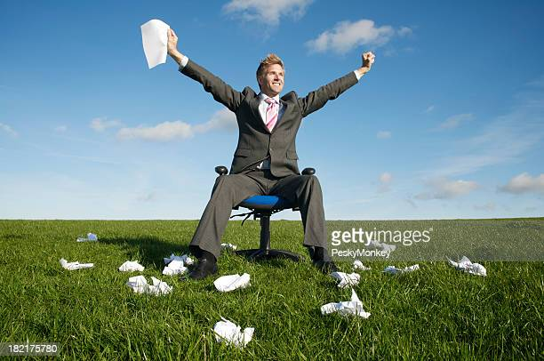 Businessman Celebrating in Meadow Holding Paper