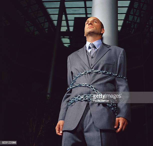 Businessman Chained to a Pole
