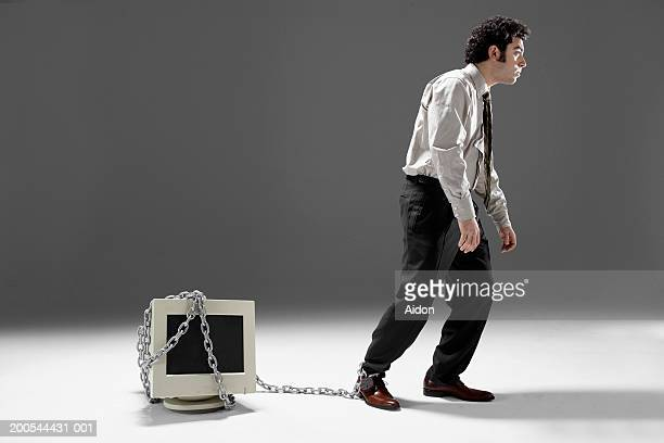 Businessman chained to computer monitor, walking like cave man, studio shot