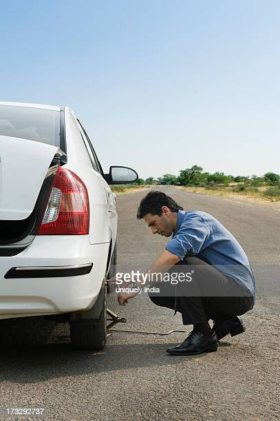 businessman changing the punctured tire of his car - puncturing stock pictures, royalty-free photos & images