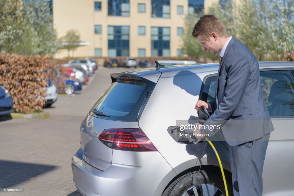Businessman charging electric car at charging point in business park : Stock Photo