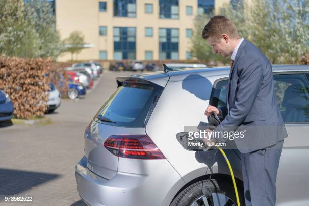 businessman charging electric car at charging point in business park - electric vehicle charging station stock photos and pictures