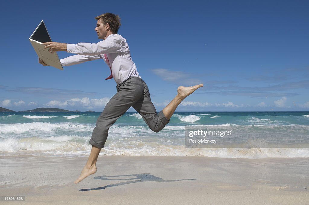 Businessman Chases Laptop on Beach : Stock Photo