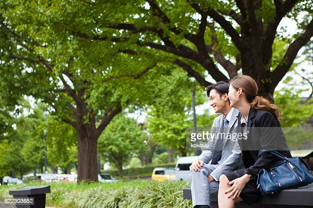 Businessman chatting with a lover while sitting in the park