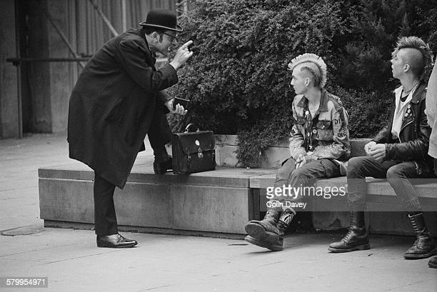 A businessman chatting with two punks in London 27th September 1984