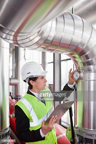 Geschäftsmann, die Feinheiten auf pipes in Fabrik